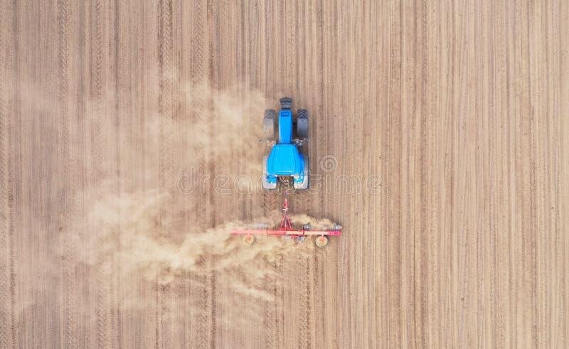 Top aéreo abajo de la opinión sobre el tractor azul que tira de una paleta, preparando un suelo para la siembra de la semilla, tr fotos de archivo libres de regalías