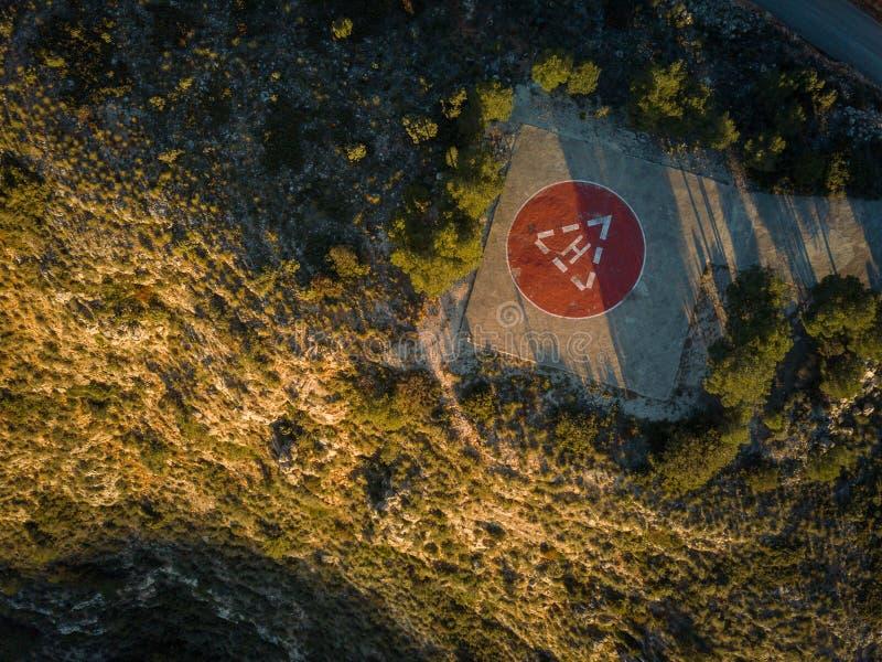 Top aéreo abajo de la vista del cojín de aterrizaje del helicóptero en montañas durante salida del sol de oro imagen de archivo libre de regalías