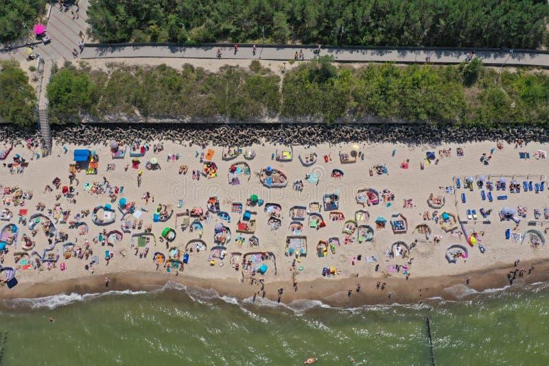 Top aéreo del abejón abajo de la opinión sobre la playa soleada con los persona que toma el sol con los guarda-brisas y las toall fotos de archivo