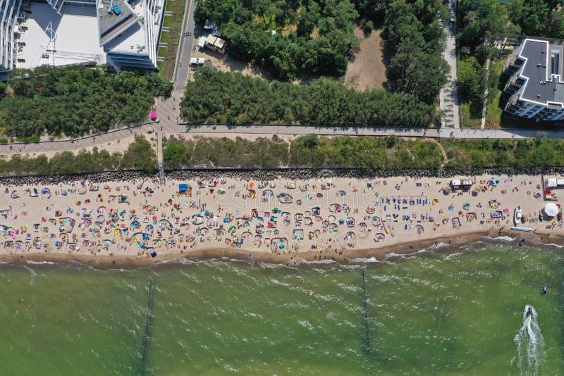 Top aéreo del abejón abajo de la opinión sobre la playa soleada con los persona que toma el sol con los guarda-brisas y las toall fotografía de archivo