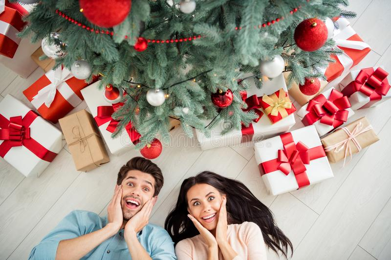 Top above angle photo of two impressed people having giftboxes for christmas enjoy x-mas party lying on floor in house. Top above angle photo of two impressed royalty free stock images