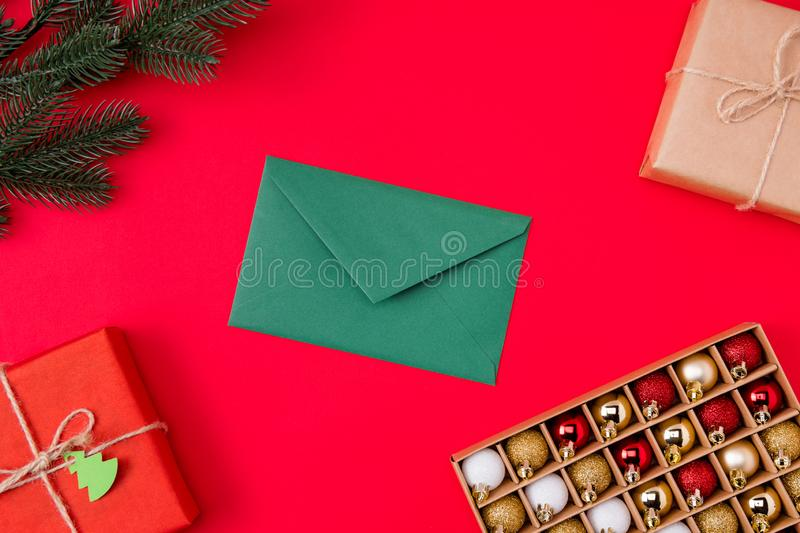 Top above high angle view photo of green envelope surrounded with gifts presents branch of fir tree and box of christmas stock photo