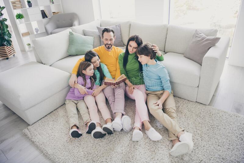 Top above high angle view photo of positive cheerful fun family sit floor carpet near sofa couch dad read book mom three stock photos