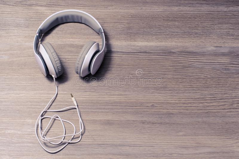 Top above overhead close up view photo of beautiful modern stylish comfortable good nice headset. White headphones on a table, iso. Lated on wooden background royalty free stock photo