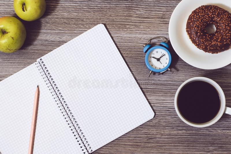 Top above overhead close up view photo of open diary notebook notepad book writing pen pentic for making notes green fresh fruit a royalty free stock image