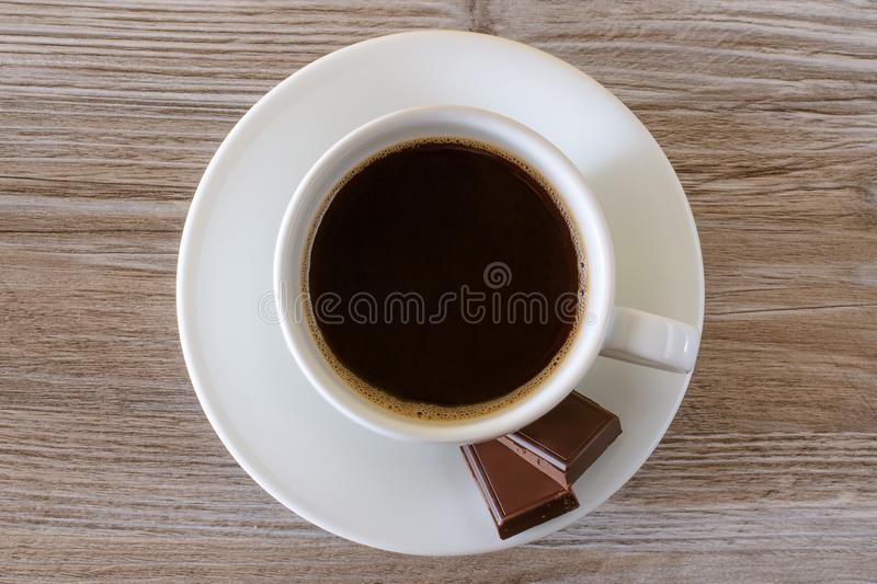 Top above overhead close up view photo of tasty aromatic fresh morning dark hot coffee espresso with foam and two peaces of cholol royalty free stock photography