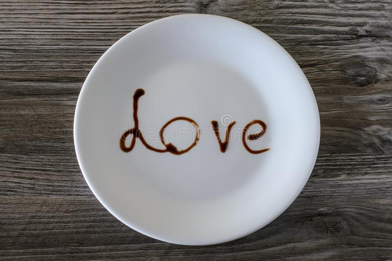 Top above overhead close up view photo of white round plate with write inscription i love you concept. A plate with word love on i stock photo