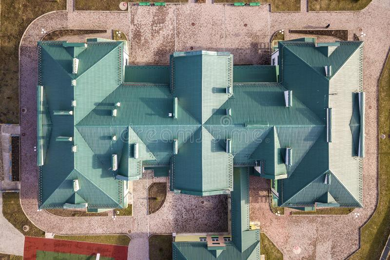 Top aerial view of building green shingle tiled roof with complex configuration construction. Abstract background, geometrical royalty free stock images