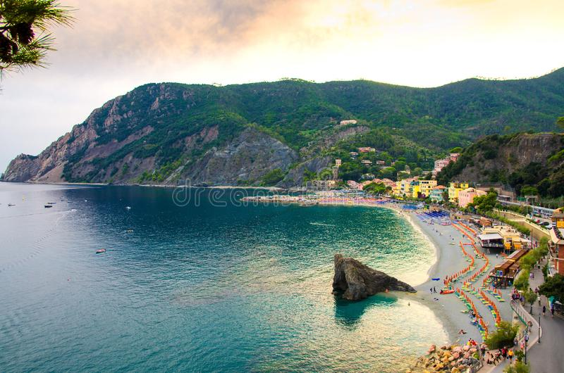Top aerial view of green hills, rocks, harbor and beach of Monterosso town village at sunset dusk, Genoa Gulf, Ligurian Sea, Natio stock photo