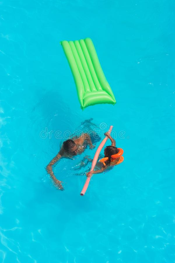 Top, aerial view of a man with his daughter playing in the pool stock photo