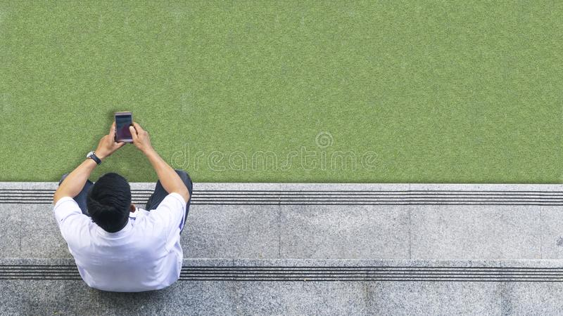 Top aerial view of the man in white shirt uses mobile phone. The top aerial view of the man in white shirt uses mobile phone and sits on the pedestrian concrete stock image