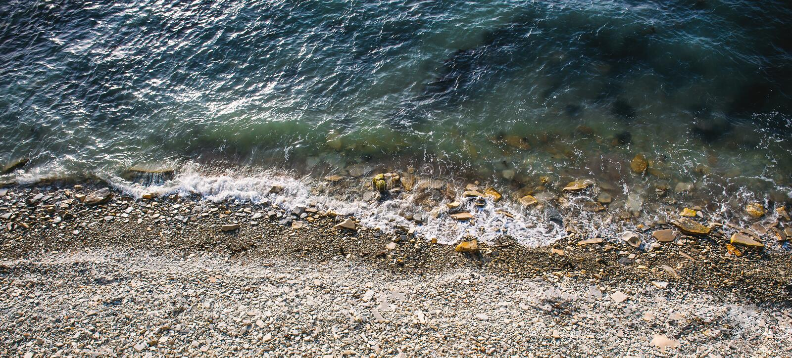Top aerial view of sea water and stone shore or rocky coast. Ocean waves landscape background stock photos