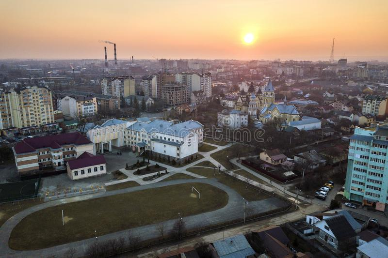 Top aerial view of urban city landscape. Apartment buildings, school, football field, church and houses on pink sky at sunrise. Background royalty free stock photo