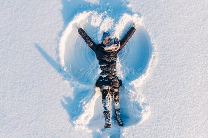 Top aerial view of young happy smiling girl making by arms snow angel figure and lying in snow, winter outdoor activity stock photos