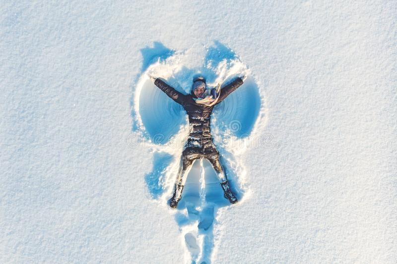 Top aerial view of young happy smiling girl making by arms snow angel figure and lying in snow, winter outdoor activity stock images