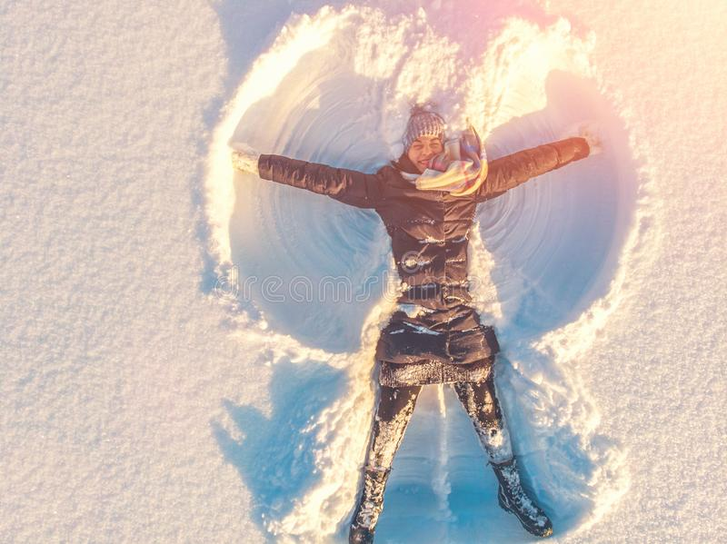 Top aerial view of young happy smiling girl making by arms snow angel figure and lying in snow, winter outdoor activity stock photo