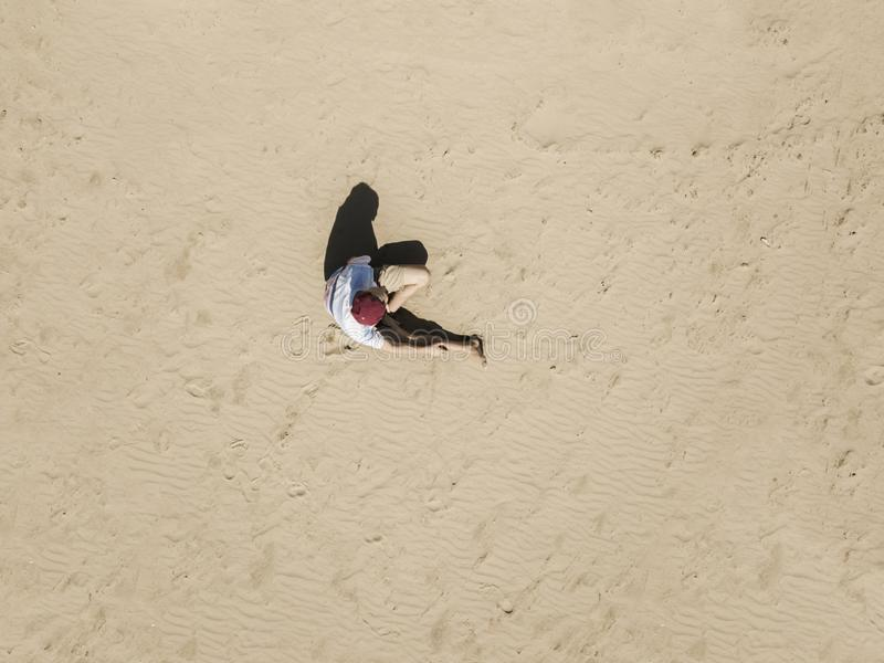Top aerial view of young hipster sitting on the abstract sandy sea beach. summer exotic concept d stock photography