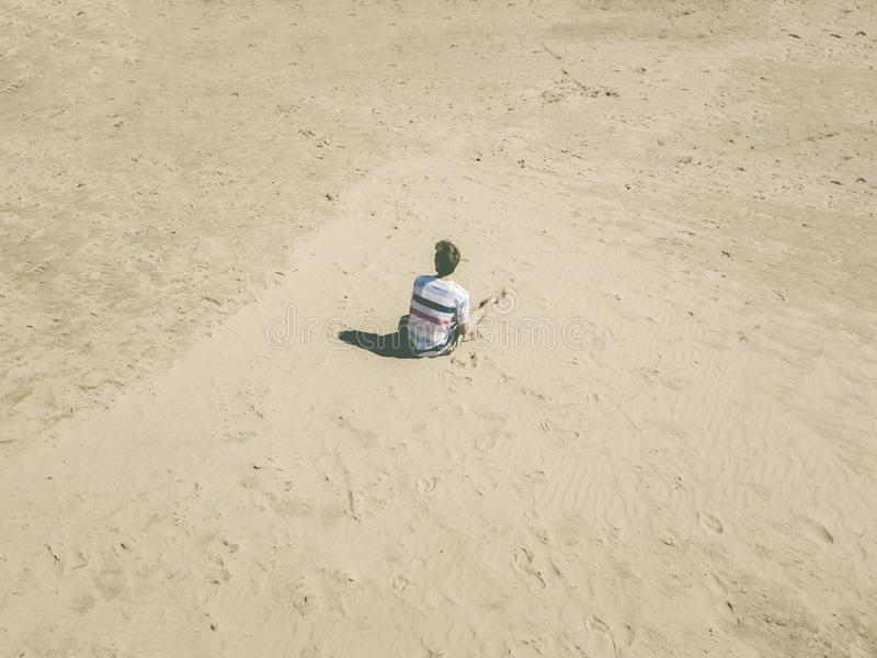 Top aerial view of young hipster sitting on the abstract sandy sea beach. summer exotic concept d stock photos