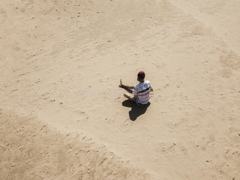 Top aerial view of young hipster sitting on the abstract sandy sea beach. summer exotic concept d stock image