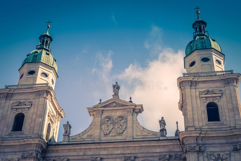 Top of ancient church with symbols of religion blue sky background in Salzburg Austria toning. Top of ancient large church with symbols of religion blue sky stock photo