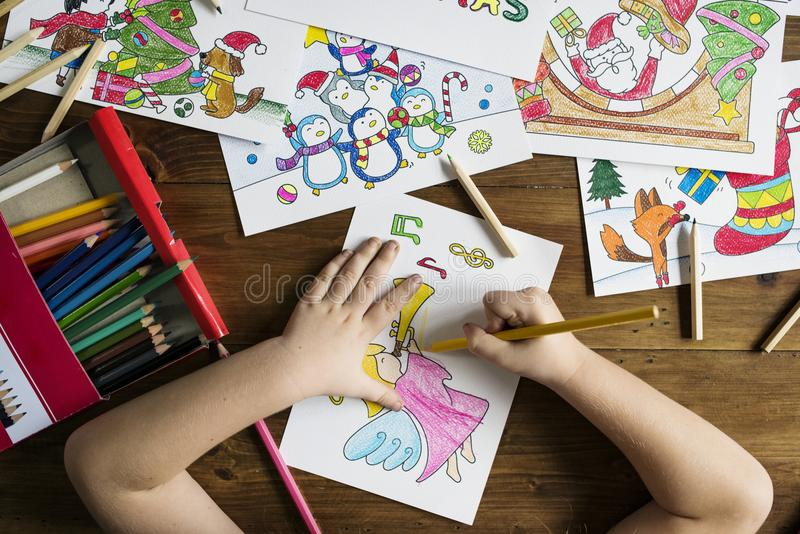 Top Angle Photo of Child Holding Pencil While Drawing Female Angel Playing Wind Instrument royalty free stock photo