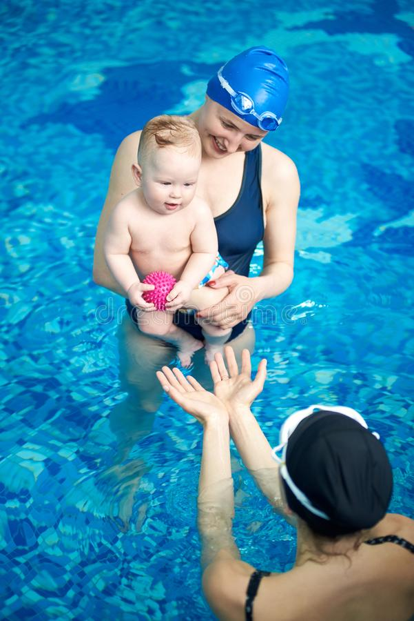 Top angle view of mom standing in pool, holding son in arms and laughing while another woman playing ball with her kid royalty free stock photos