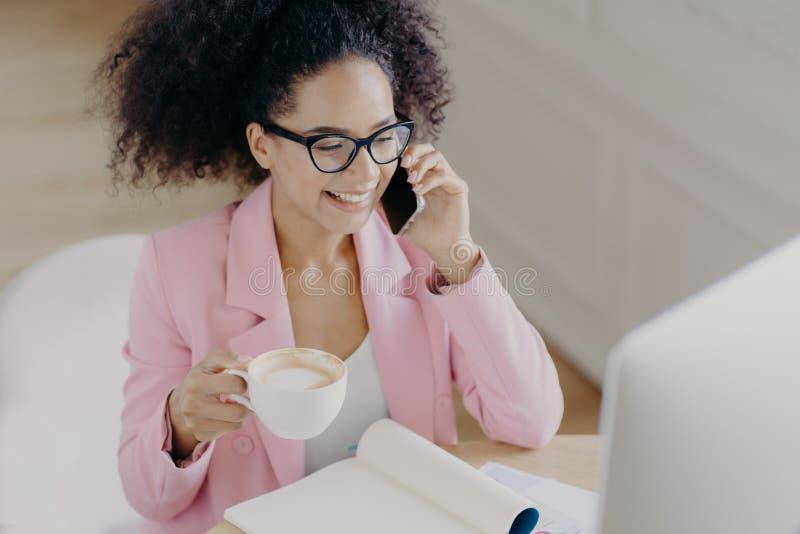 Top-Ansicht der frohen dunkelhäutigen Frau mit lockig dunklen Haaren, hat Telefongespräche, hält Schlamm zu trinken, lächelt ange lizenzfreies stockbild
