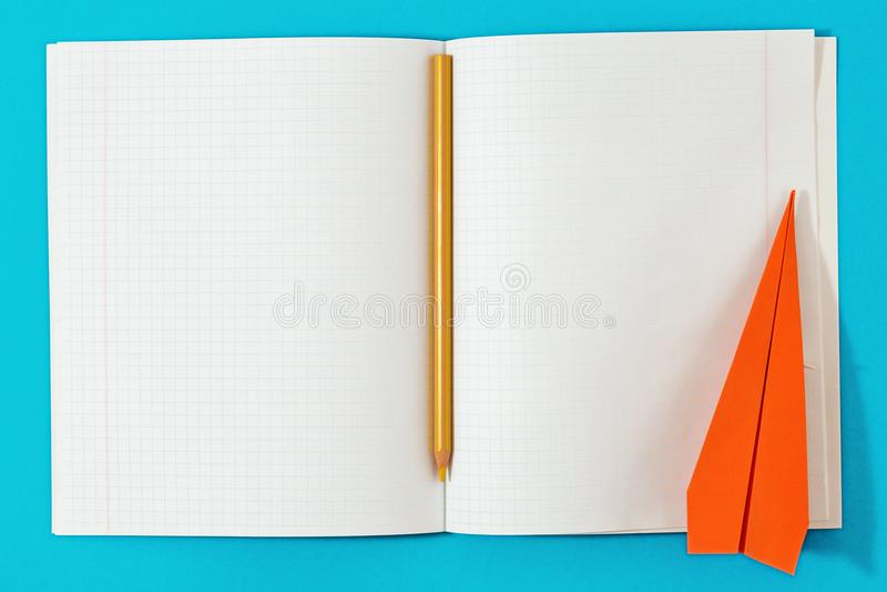 Top azul abierto del fondo del aeroplano de papel del lápiz del cuaderno de la endecha plana fotos de archivo libres de regalías