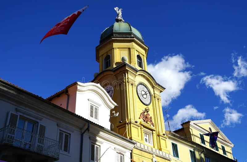 The city clock tower on sunlit in the Croatian town of Rijeka, the European Capital of culture 2020. The top of baroque city clock tower with sculpture of a stock image