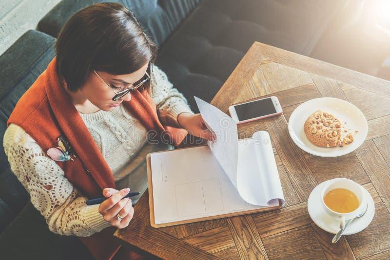 Top beskådar Den unga attraktiva kvinnan sitter i kafé på tabellen och skriver pennan, fyller ut frågeformuläret, undertecknar en royaltyfri bild