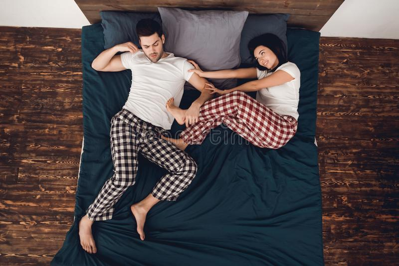 Top beskådar Den unga härliga kvinnan i pajama skjuter den vuxna sova mannen från säng arkivbild