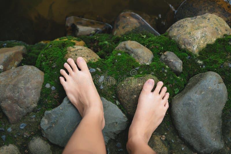 Top beskådar foten av kvinnaställningen på vått vaggar golvet med grön mossa royaltyfria foton