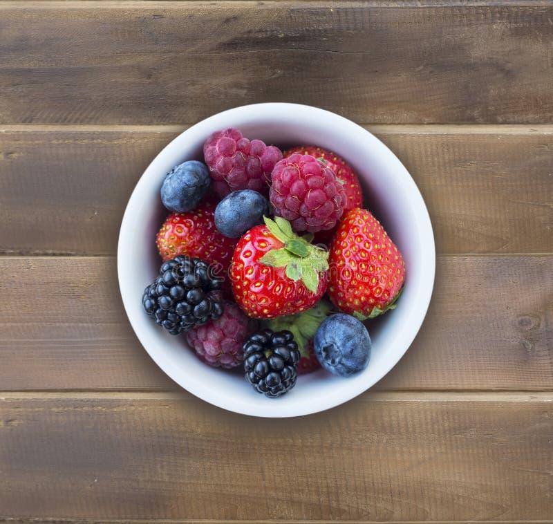 Top beskådar Frukter och bär i bunke på träbakgrund Mogna hallon, jordgubbar, björnbär och blåbär arkivbild