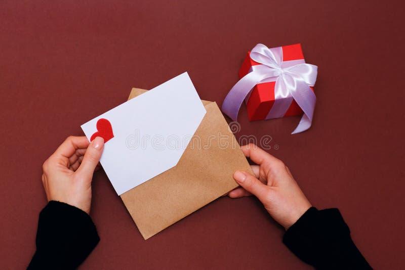 Top beskådar Hand av bokstaven för flickahandstilförälskelse på Sankt valentindag Handgjord vykort med det röd hjärta formade dia royaltyfri bild