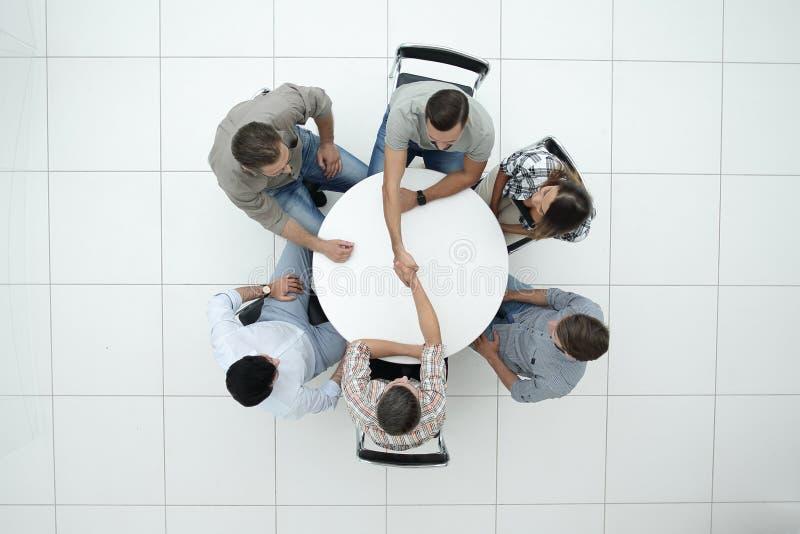 Top beskådar handskakningkollegor på den runda tabellen arkivfoton