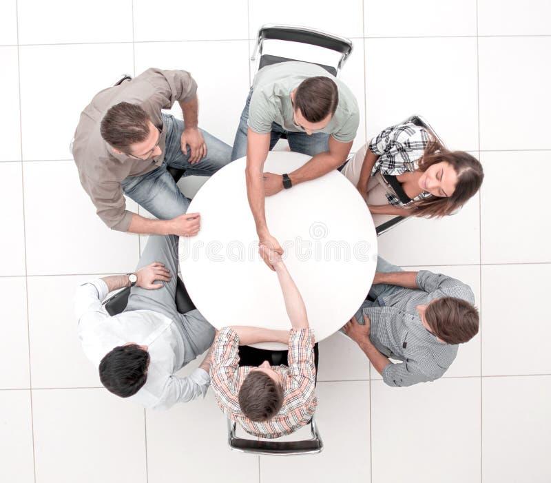 Top beskådar handskakningkollegor på den runda tabellen royaltyfria foton
