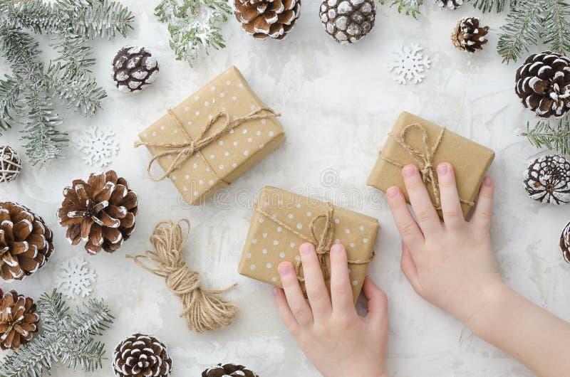 Top beskådar Lägenheten lägger barns händer rymmer gåvaaskar, kottar, repet, granfilialer och snöflingor på vit bakgrund royaltyfri foto