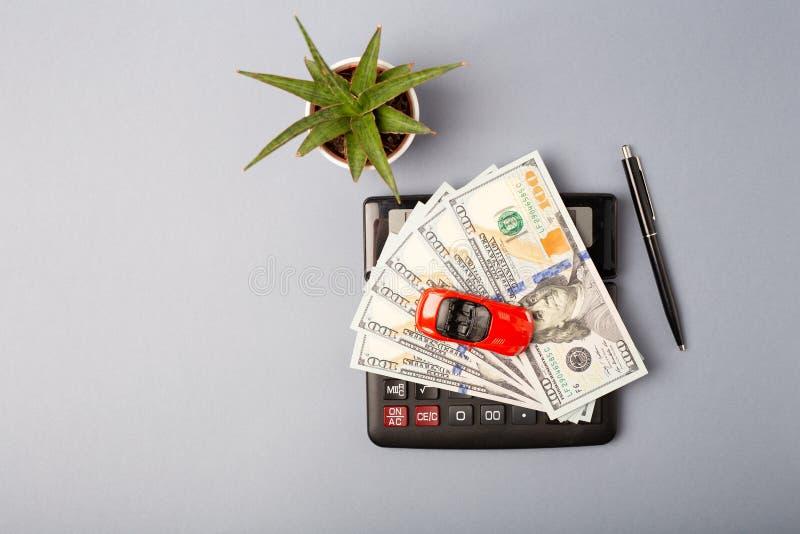 Top beskådar Liten röd bil över räknemaskinen och högen av pengardollar Kostade beräkningskostnader för lånkostnader och royaltyfri bild