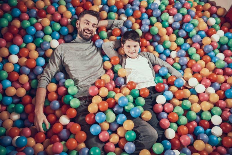 Top beskådar Lycklig farsa och son i pöl med bollar arkivbild