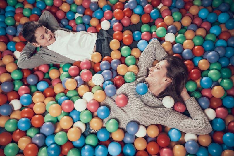 Top beskådar Lycklig mamma och son i pöl med bollar royaltyfria foton