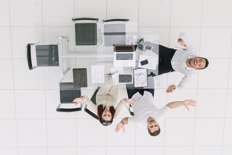 Top beskådar Lyckliga anställda som sitter på kontorsskrivbordet arkivbild