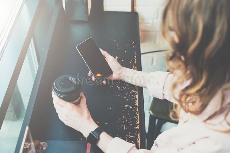 Top beskådar Närbild av smartphonen och koppen kaffe i händer av hipsterflickasammanträde i kafé på den svarta tabellen royaltyfri foto