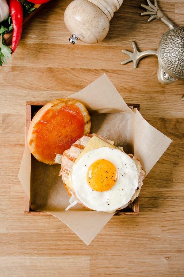 Top beskådar Slut upp den mini- hamburgaren Läcker hamburgare med stekt ägg, grönsallat, ost, ketchup och bröd på ett trä royaltyfria foton