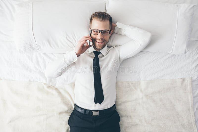 Top beskådar Stilig affärsman med exponeringsglas på säng som kallar från hans telefon royaltyfri fotografi