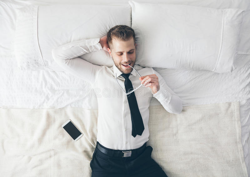 Top beskådar Stilig affärsman med exponeringsglas som ligger på säng arkivfoton
