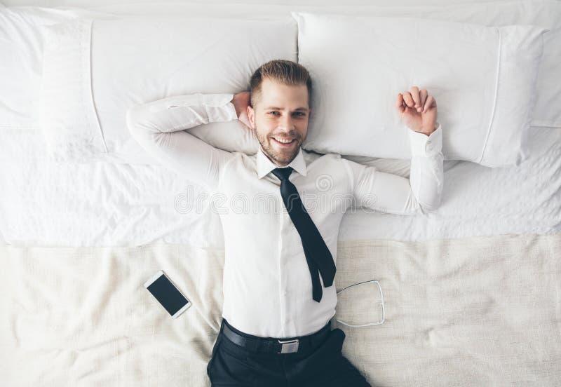 Top beskådar Stilig affärsman som kopplar av på säng efter en tuff dag på arbete arkivbild