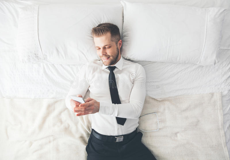 Top beskådar Stilig affärsman som ligger på säng som smsar från hans smartphone royaltyfri fotografi