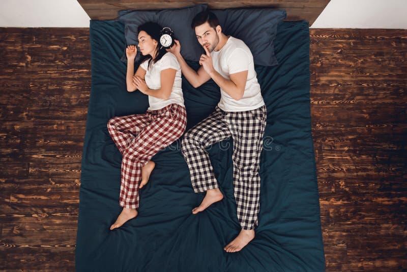Top beskådar Vuxna stiliga manplan som vaknar upp med ringklockan som sover den unga kvinnan som ligger på säng fotografering för bildbyråer