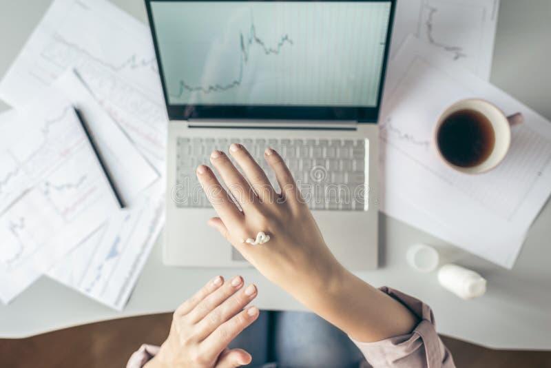 Top besk?dar affärskvinna som sitter på tabellen och applicerar handkräm som arbetar på bärbara datorn med diagram och diagram so royaltyfri bild