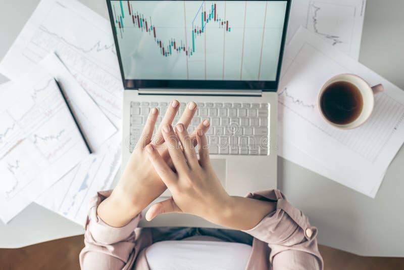 Top besk?dar affärskvinna som sitter på tabellen och applicerar handkräm som arbetar på bärbara datorn med diagram och diagram so arkivfoton